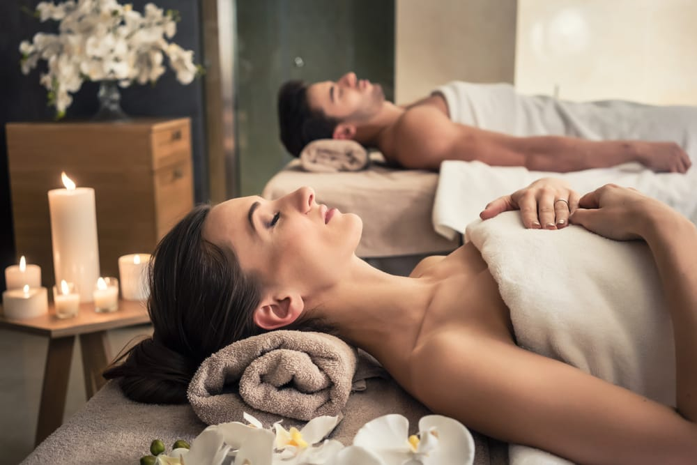 Image of man and woman laying on table prepared to receive massage therapy