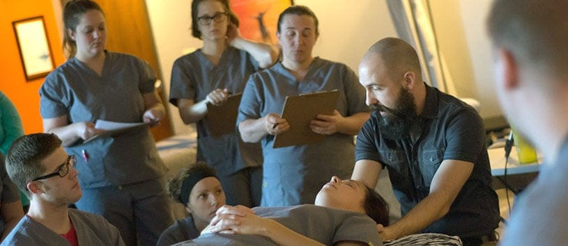 Instructor Jason Craft demonstrating to a massage therapy class