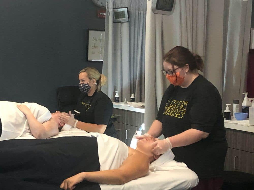 This is an image of esthetics students performing facials on clients in the clinic. Students are wearing masks for due to COVID.