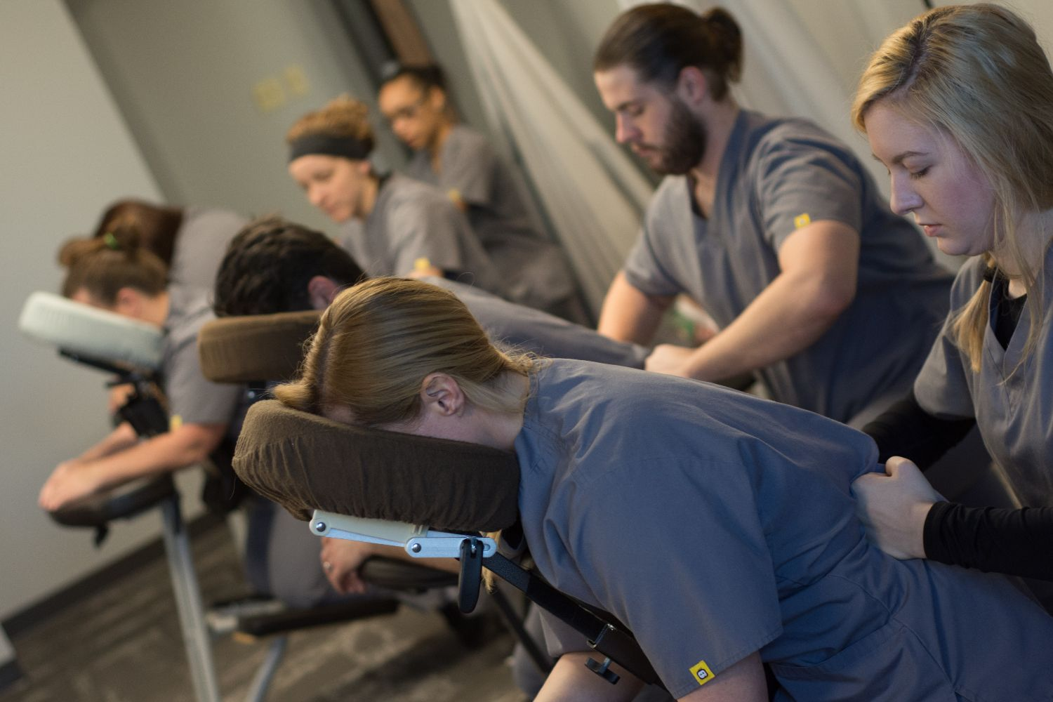 This is an image of massage students in massage chairs receiving massages from other students to practice their skills.
