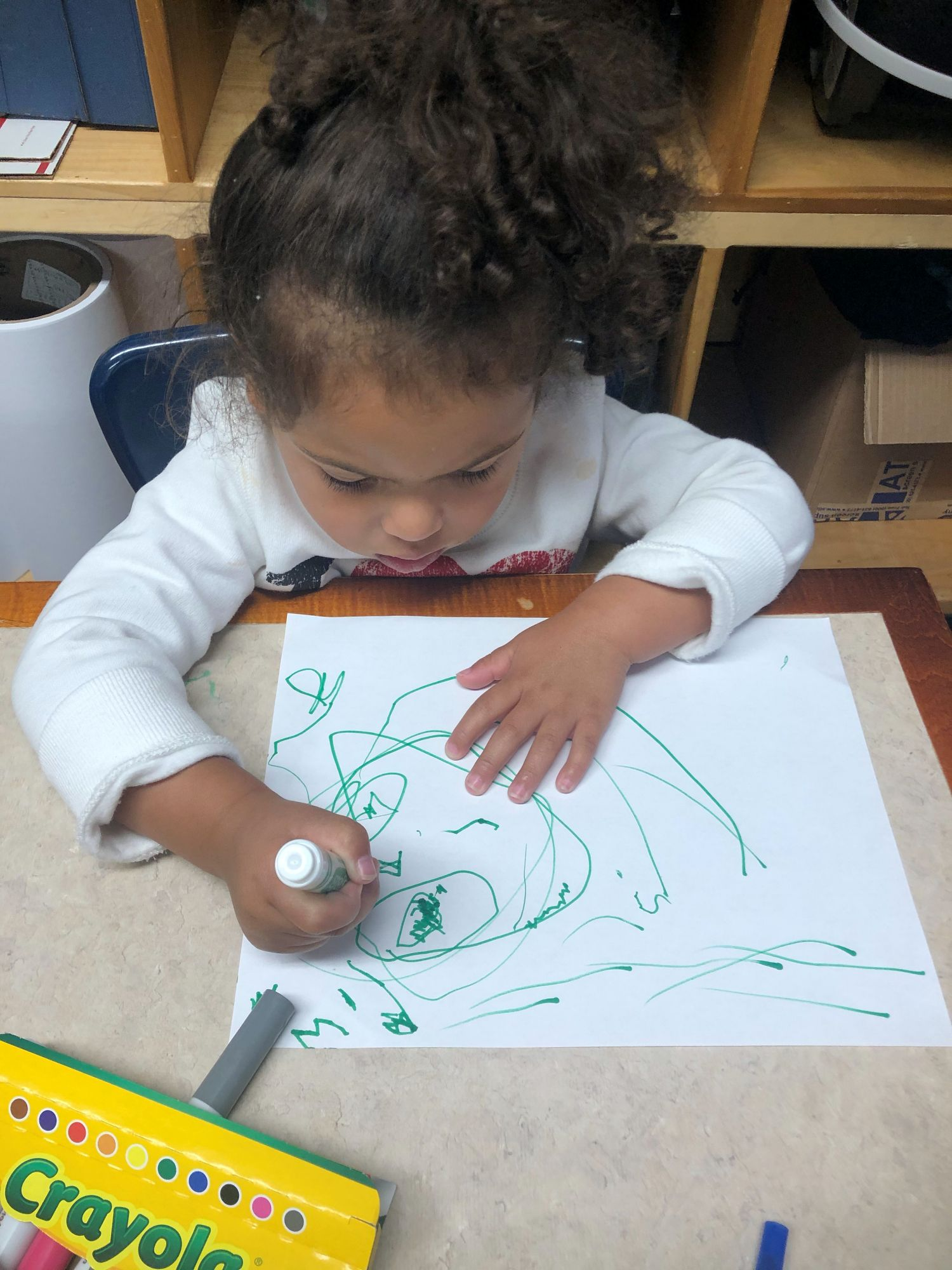 Picture Of Child Sitting At Desk Coloring With Markers